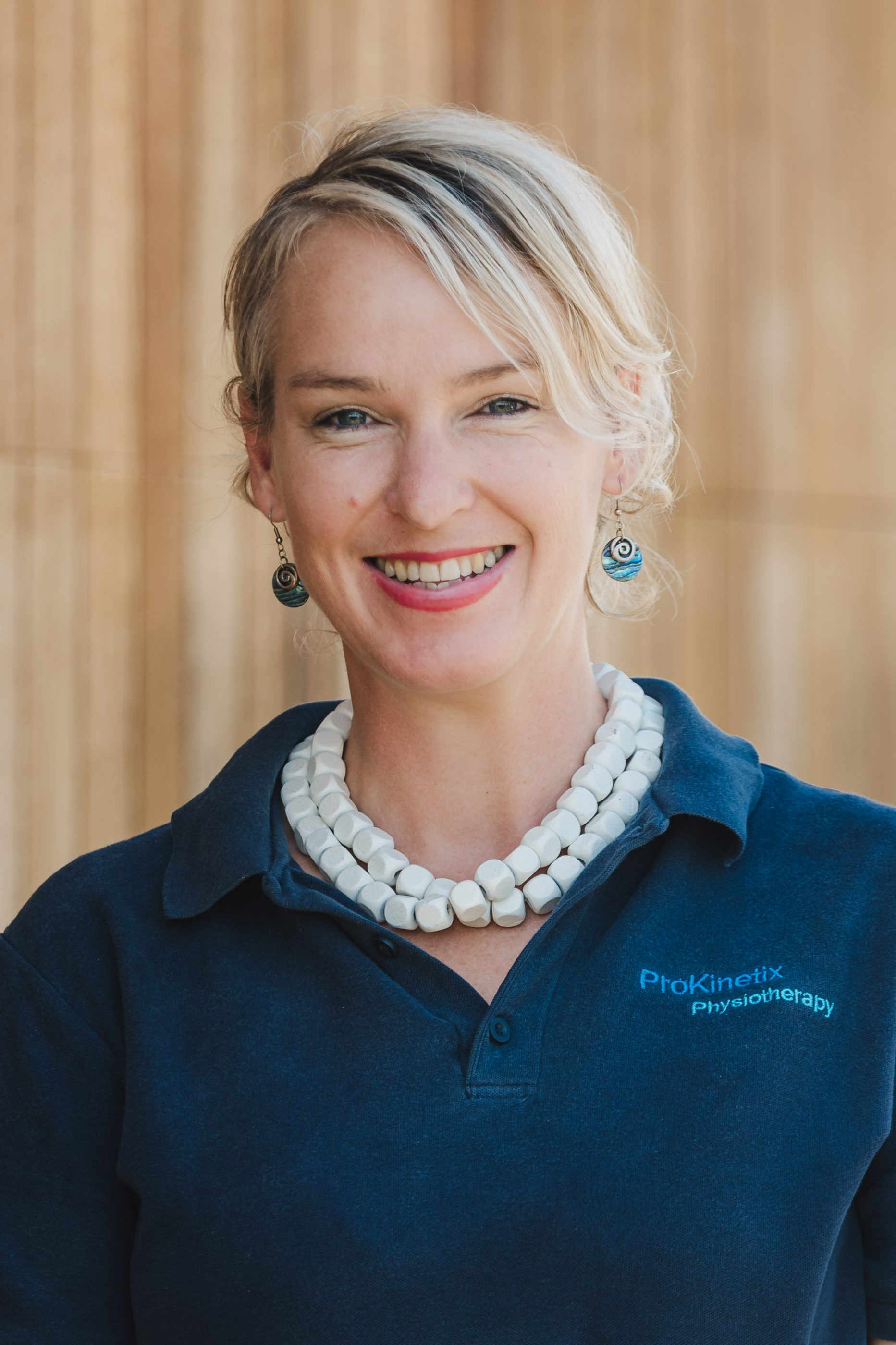 """Photo of a blonde woman wearing a white necklace, paua shell earring, and a blue polo shirt that reads, """"ProKinetix Physiotherapy"""". She is smiling."""